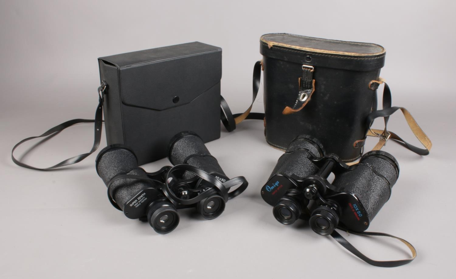 Two cased pairs of binoculars. Includes Super Zenit 20x50 and Omiya 10x50. Interior optics of