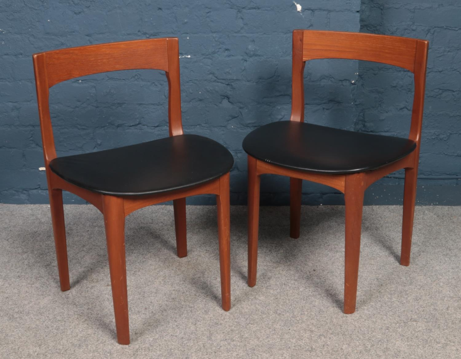 A pair of retro teak chairs. With vinyl covered seats.