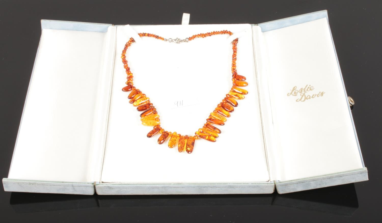 A cased cognac amber necklace comprising approximately 150 shaped and graduated beads with safe lock - Image 2 of 2