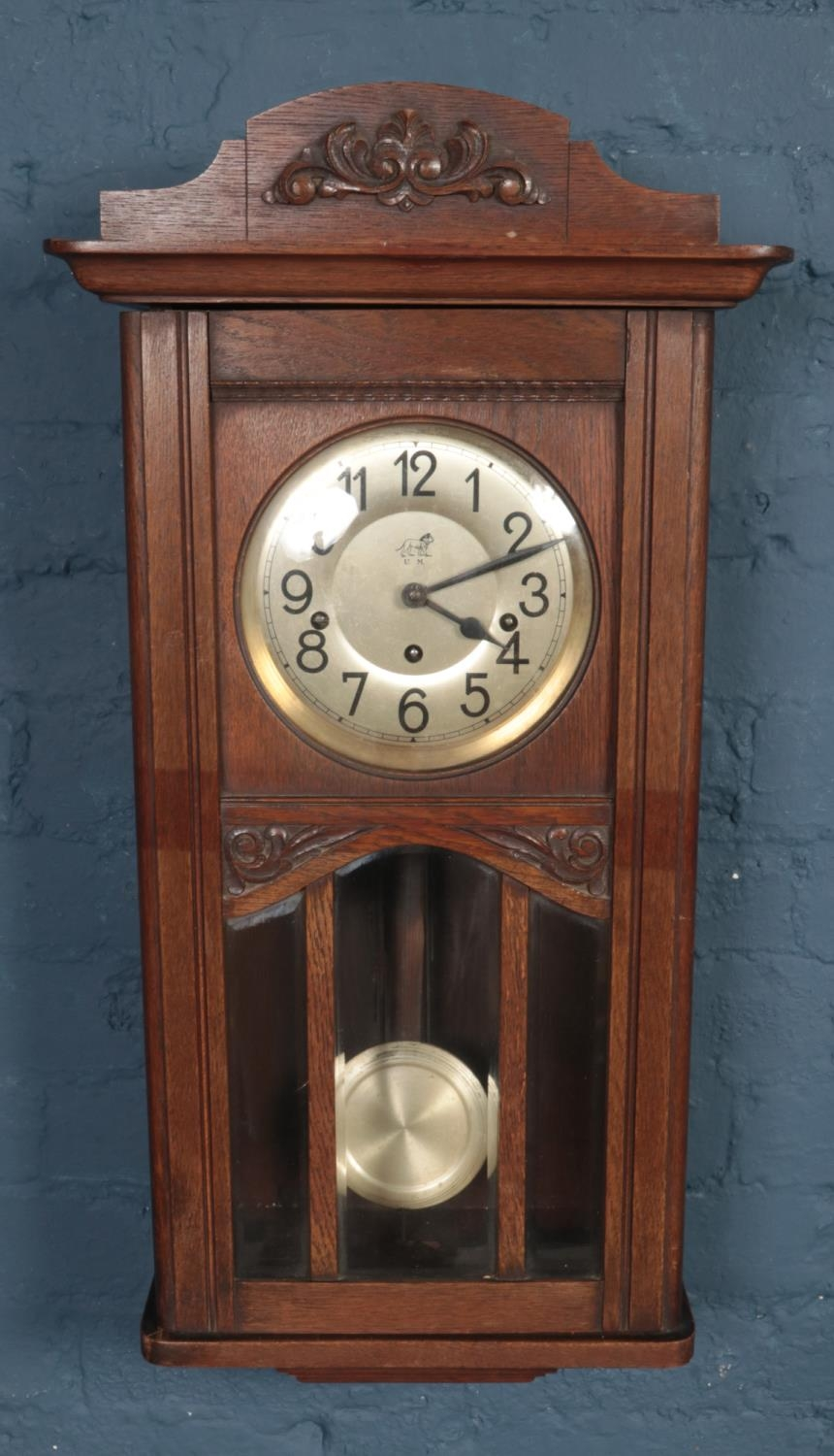 A carved oak Muller & Co. wall clock.