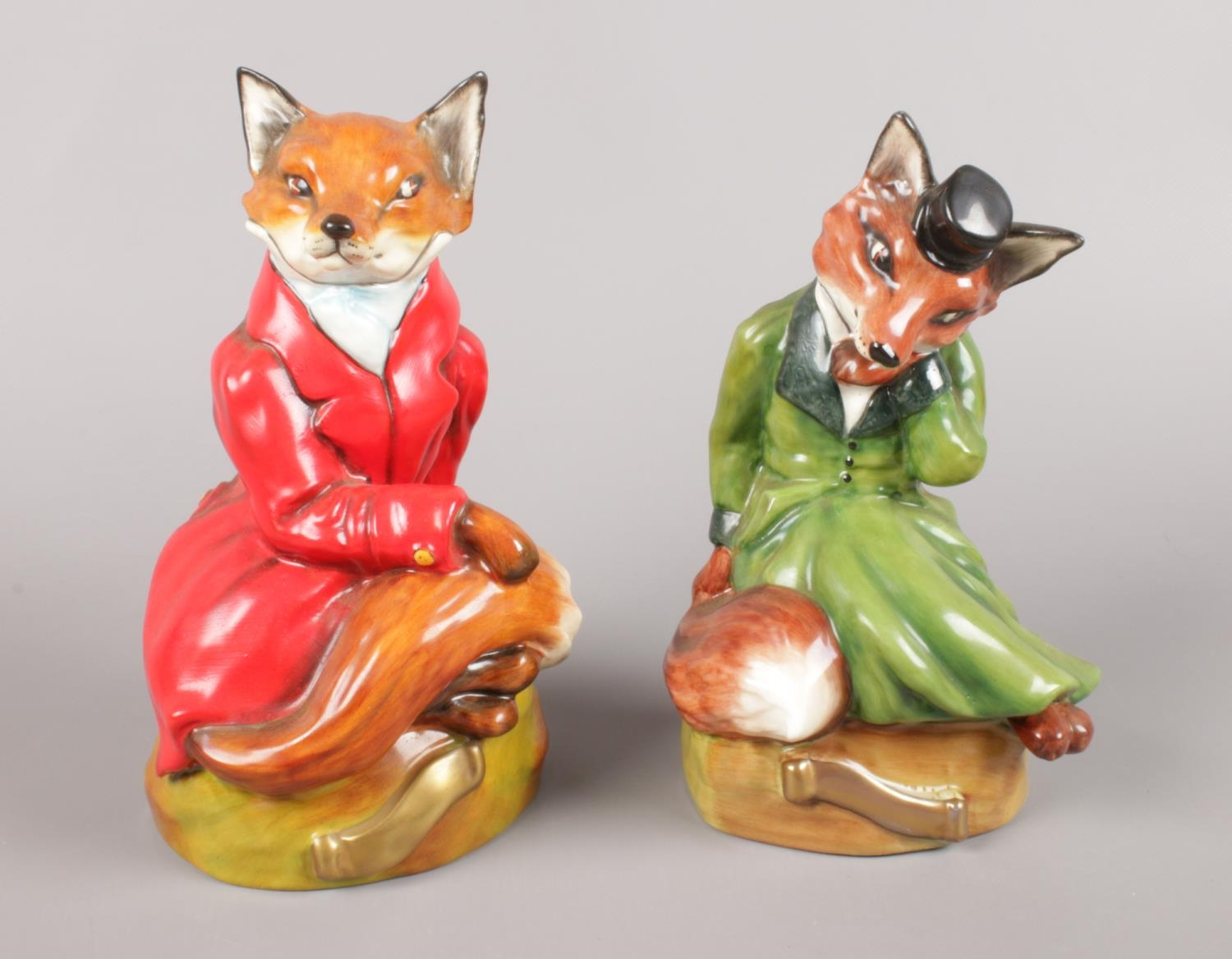 A pair of Bloor China (Stoke-On-Trent) Green and Red Seated Fox Figures. Red Figure - H:19cm Green