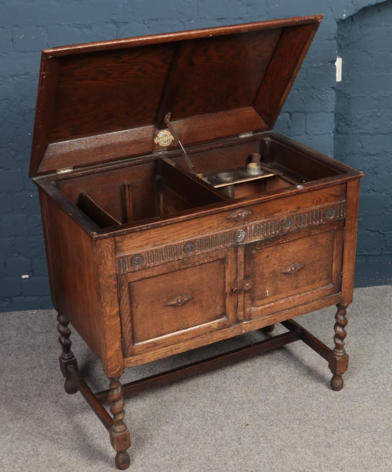 A carved and paneled oak Gilbert gramophone cabinet on barley twist supports.