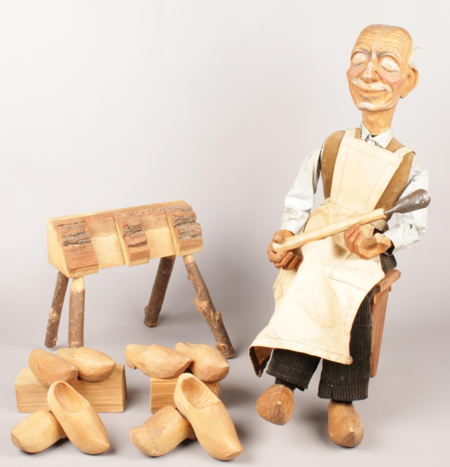 A carved wooden cobbler shop display model. Includes wooden bench and an assortment of wooden