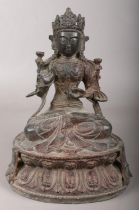 A Chinese bronze devotional figure raised on lotus plinth. 23cm.