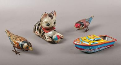 A group of tin plate toys. Kitten with ball, two birds, speed boat.