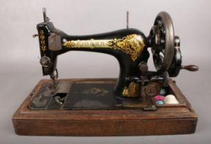 A wooden cased Singer sewing machine. Model no V1212329.