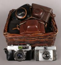 A Wicker Basket containing Eight Cameras, Five of which are Film. Examples include Petri 7 S and