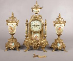 A decorative brass mounted clock garniture, decorated with scenes of courting couples.
