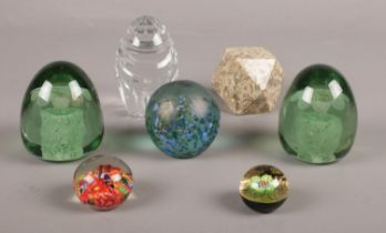 A group of mostly glass paper weights. various sizes & styles.