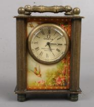 A miniature brass carriage clock. With erotic glass panels. 7cm tall. Missing winder.