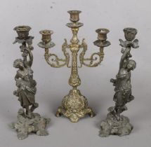 A Pair of Cast Metal Decorative Figural Candlesticks, together with another Brass Example. Some