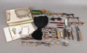 A box of assorted collectables. To include a group of vintage spectacles, two tin-plate vehicles,