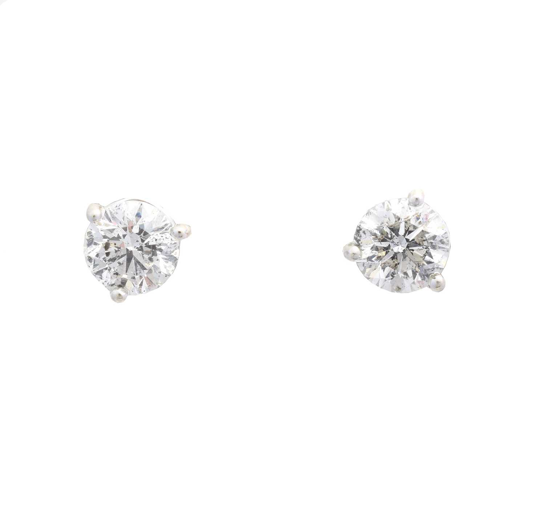 A pair of brilliant cut diamond stud earrings,