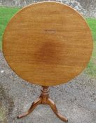 An antique mahogany circular tilt top table, raised on a turned column to a triform base, diameter