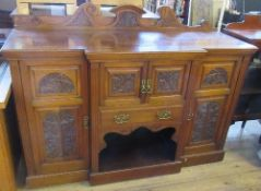 An Edwardian mahogany break front side board, fitted with a cupboard, over a drawer, over a shelf,