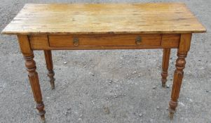 An antique pine side table, fitted with a frieze drawer and raised on turned legs, 43ins x 17.5ins x