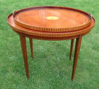 A mahogany and satinwood inlay oval table, the top with galleried sides, raised on square tapering