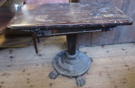 A 19th century rosewood fold over games table, with carved decoration, and raised on a column to a