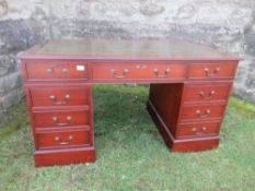 A reproduction pedestal desk, having leather writing surface, and drawers around the knee hole,