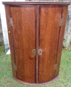 An antique oak corner cupboard, with mahogany banding, the barrel front opening to reveal shelves,