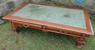 A mahogany low coffee table, with leather inset top, the carved frieze with drawers raised on carved