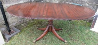 A mahogany tripod dining table, raised on a column with four reeded legs, length closed 54ins,