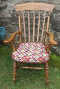 A Windsor style open armchair, with stick back, having turned supports to the shaped arms