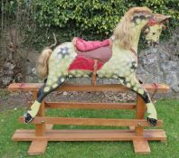 A carved and painted rocking horse, dapple grey horse, with leather and upholstered saddle, on a