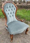 A Victorian show wood nursing chair, with carved and button spoon back, raised on short cabriole