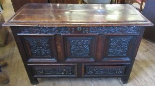An antique oak mule chest, with rising lid, the front carved with flowers and leaves, fitted with