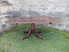 A 19th century mahogany tilt top breakfast table, the rectangular top raised on a turned column