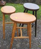 Three oval topped stools, height 21.5ins and 24ins