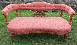 A Victorian show wood settee, with upholstered shaped top rail, having carved and turned supports to
