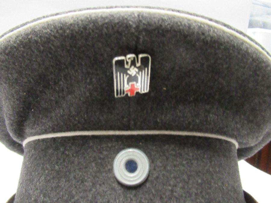 A Third Reich style visor cap, in dark grey wool, with white piping, and black leather effect chin - Image 2 of 6