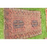 An Eastern red ground rug, decorated with repeating symbol to the field and borders, 50ins x 75ins