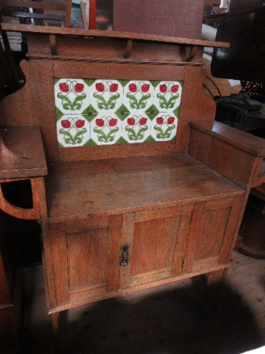 An Arts and Crafts style tile backed wash stand, with cupboard door below, width 41.5ins x height