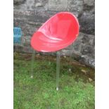 Red plastic and Perspex chair raised on metal legs