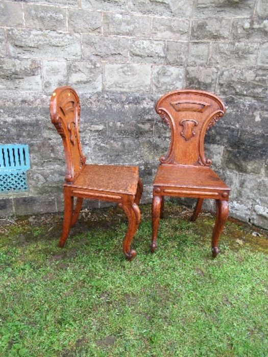 Two pairs of armorial hall chairs, in oak
