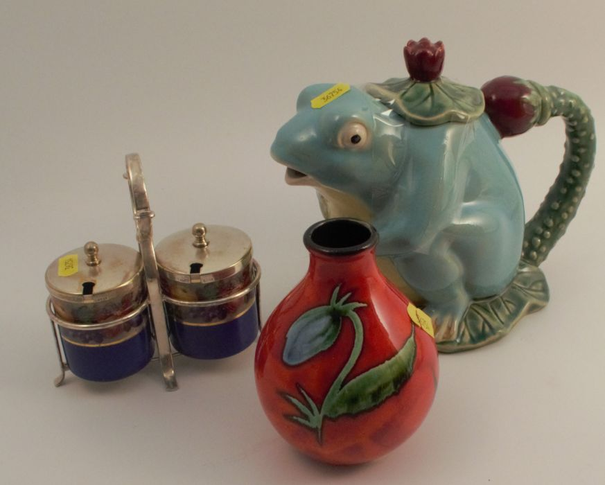 A Poole pottery vase, decorated with flowers to a red ground, together with a modern majolica frog