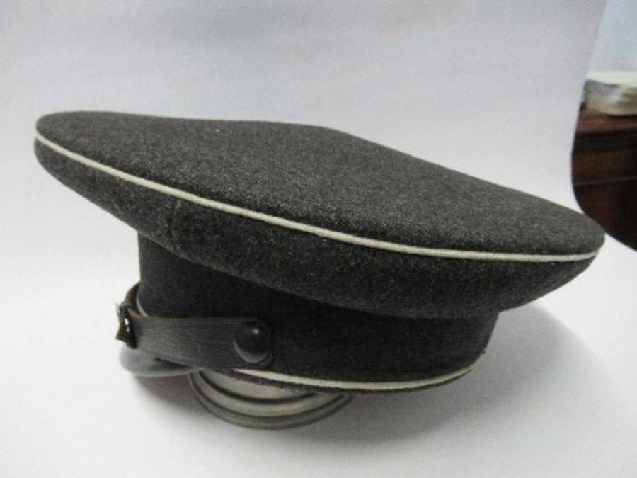 A Third Reich style visor cap, in dark grey wool, with white piping, and black leather effect chin - Image 3 of 6