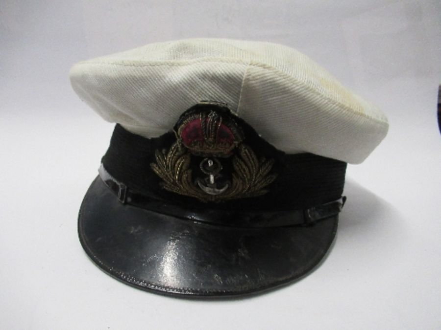 A British naval style visor cap in white cotton, with anchor and crown to the front on a black hat - Image 2 of 13