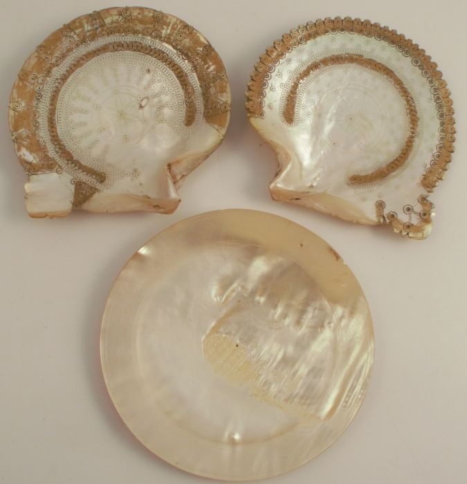 A pair of mother of pearl shells, etched with geometric patterns and traces of gilt decoration,