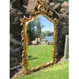 A Baroque style gilt framed mirror, of shield shaped form, max mirror size 40ins x 23ins