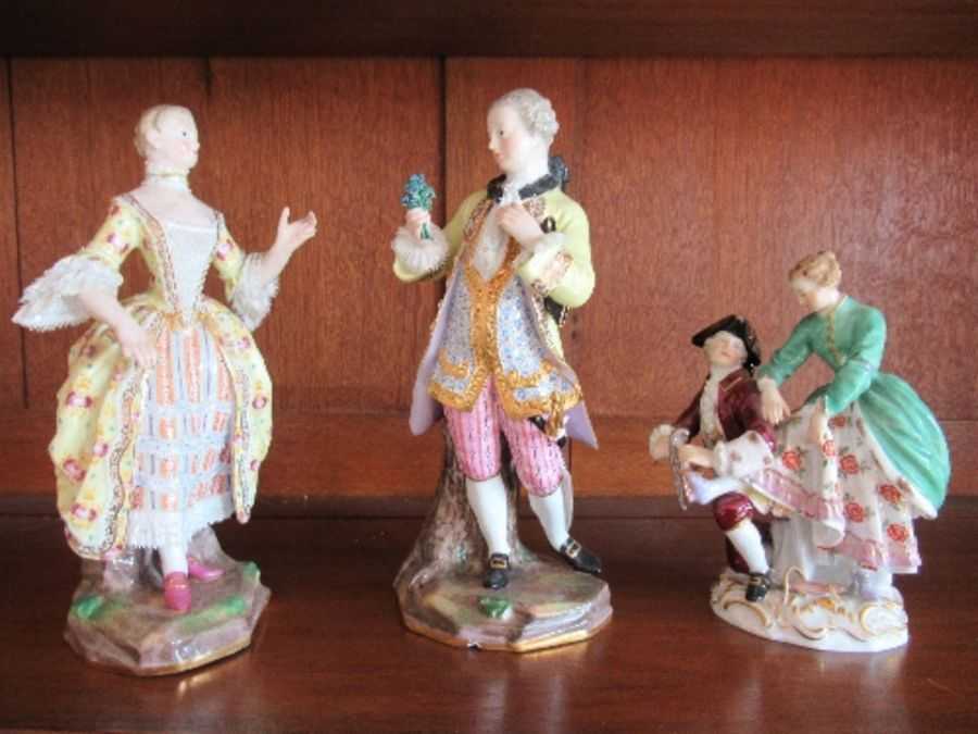 A pair of continental porcelain figures, of a man and a woman in period dress, the man holding a