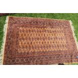 A modern Eastern design rug, decorated with repeating symbols to a gold ground, 50ins x 70ins