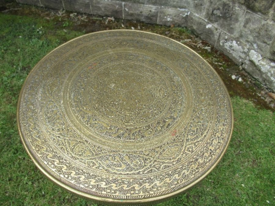 A brass Benares topped table, the wooden folding base with carved and inlaid decoration, diameter - Image 2 of 4