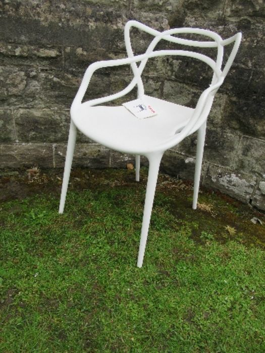 A white Kartell Masters armchair