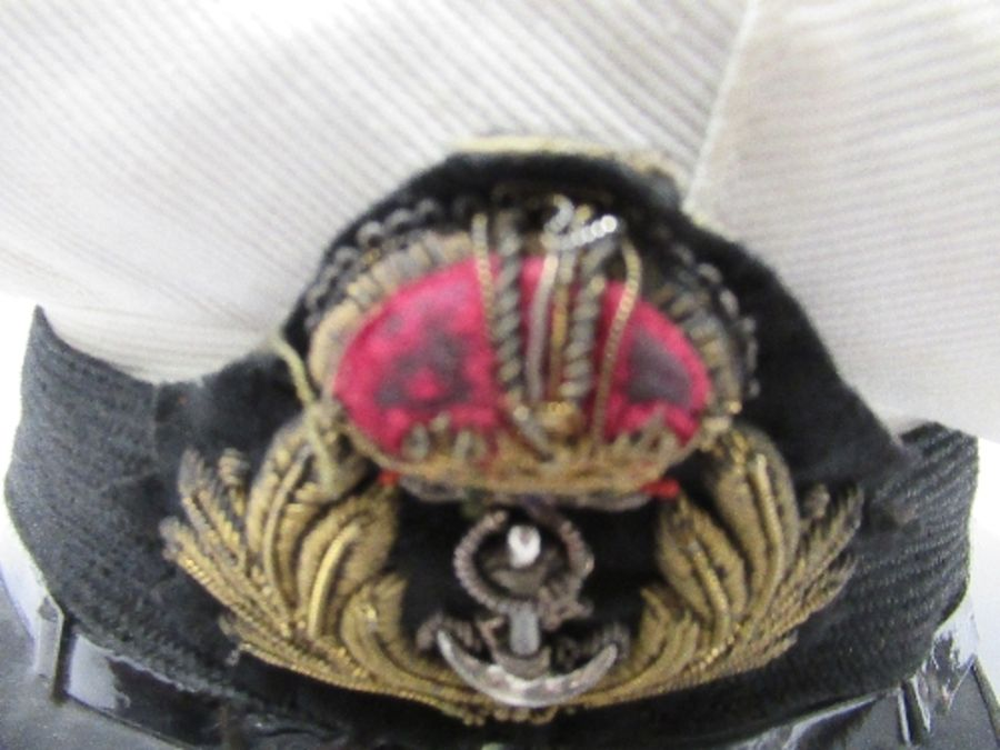 A British naval style visor cap in white cotton, with anchor and crown to the front on a black hat - Image 3 of 13
