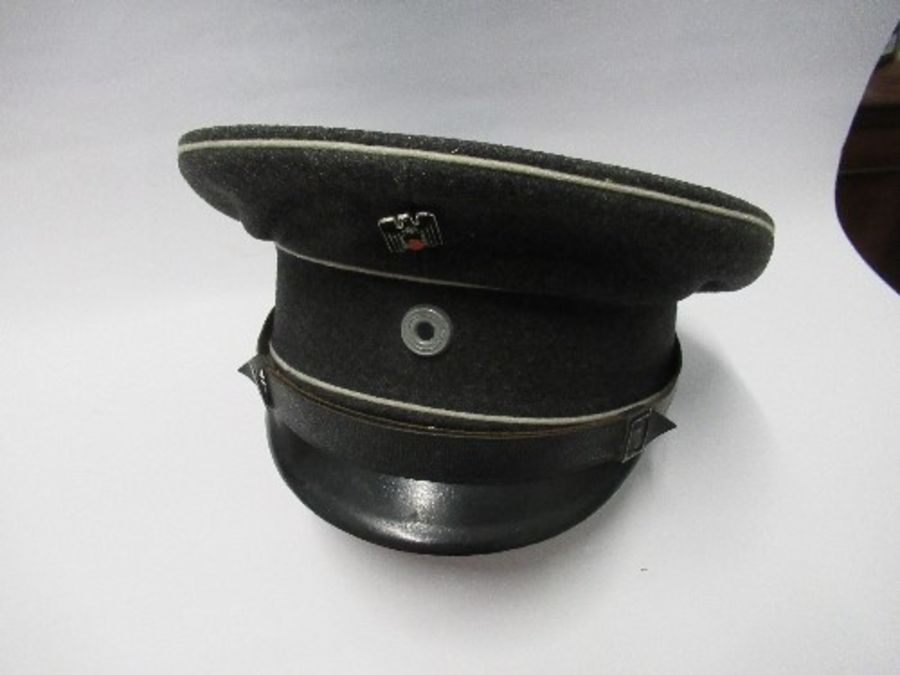 A Third Reich style visor cap, in dark grey wool, with white piping, and black leather effect chin