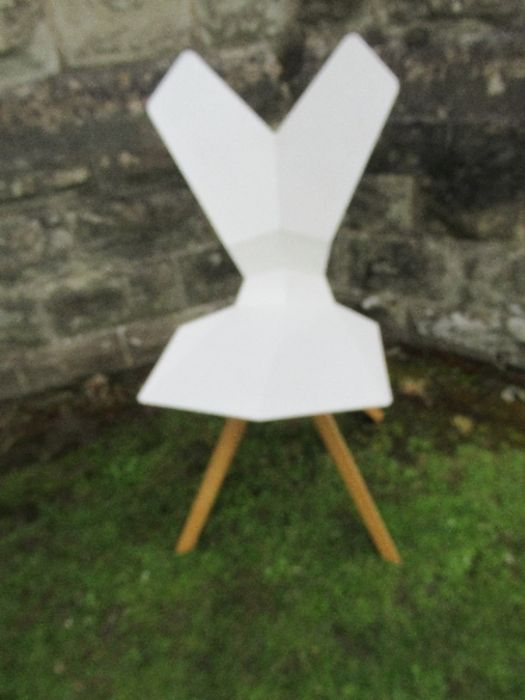A white plastic chair with geometric shaped back and seat raised on metal chairs - Image 2 of 3